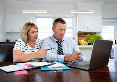 Photo of a couple by a laptop